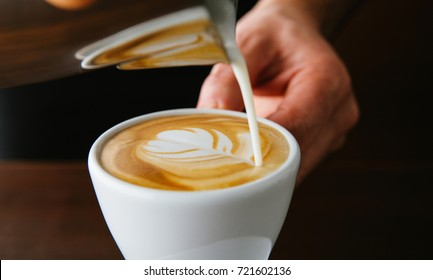 Flower Latte art. Barista pouring milk into coffee cup