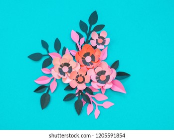Flower and leaves made of paper on a turquoise background. Handwork, favorite hobby. Pink black and blue color.