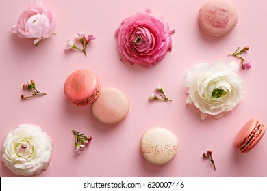 Flower and macarons pattern on a pink background. Various flower flat lay. Top view