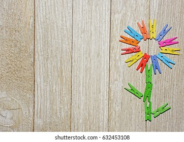 Flower made from colorful clothespins on a wooden background.  Great for crafts, scrapbooking, blogs and other project ideas.