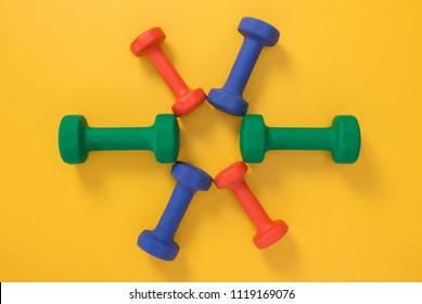 Flower made of colorful dumbbells on bright yellow background. Summer fitness concept.