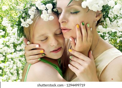 Flower manicure with my mother and daughter.Nail art.Mother and child are in nature in the summer in the flower of Gypsophila.