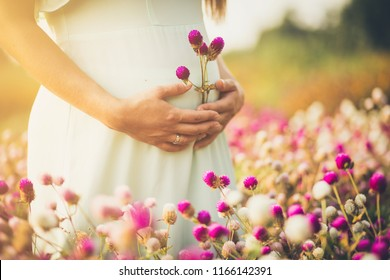 Flower of my life.  Pregnant woman standing in flowers. Close up. Copy space.