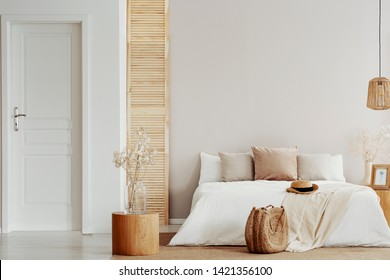 Flower on glass vase on round wooden table in beige natural bedroom, copy space on empty wall