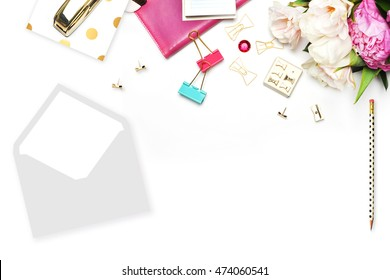 Flower on the table. Envelope and stapler. Home workplace. Table view. Business accessories. Mock-up background.Peonies. Flat lay