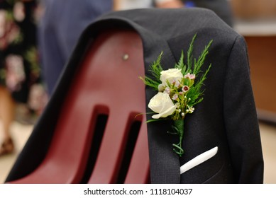 Flower ornament arrangement on suit jacket draped over red chair at party.