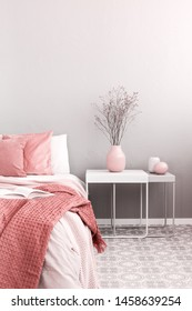 Flower in pastel pink vase on white wooden nightstand next to king size bed in trendy bedroom interior
