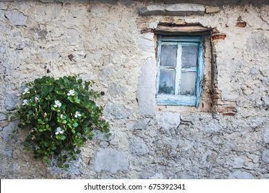 Flower pot and old window in mall village of Lubenice, Cres Island, Croatia.