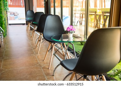 Flower pot on glass table with black share nearby mirror and green plastic grass