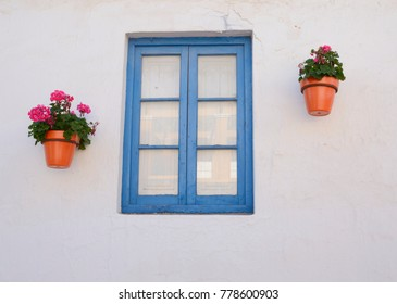 Flower pots next to blue wooden window in the old town of Estepona, Andalusia, Spain.