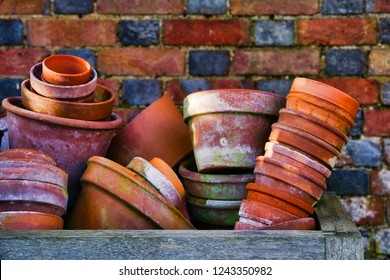 Flower pots; random piles and stacks of vintage flowerpots against brick wall
