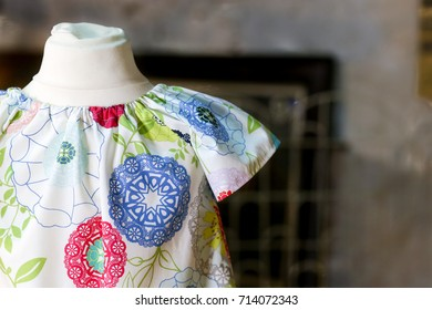Flower power kids dress wear on small antique mannequin, dark background and copy space