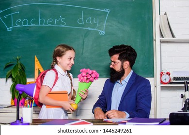 flower present for best teacher. knowledge day is 1 september. small school girl kid with flower. back to school. Happy teachers day. teachers day. Daugghter and father with flowers. happiness.