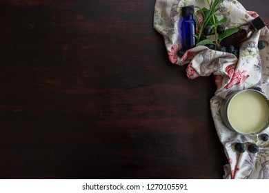 flower printed towel with bluberries, mint, rosemary, balm, and glass vials with a dark wood stained background