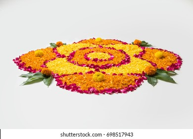 Flower Rangoli for Diwali or Pongal Festival made using Marigold or Zendu flowers and Rose petals over white background, selective focus