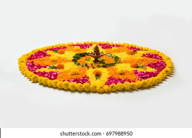 Flower rangoli for Diwali or Pongal made using marigold or zendu flowers and red rose petals over white background with Clay Oil Lamp in the middle, selective focus