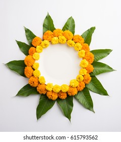 flower rangoli made using marigold or zendu flowers and mango leaves over white background with copy space in the middle, selective focus