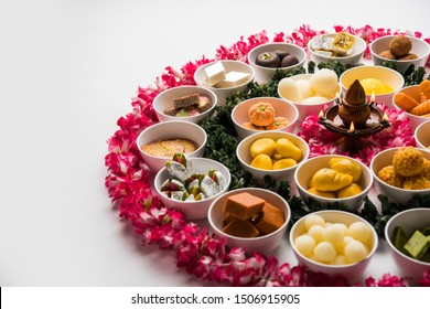 Flower Rangoli with sweets/mithai and diya in bowls for Diwali or any other festivals in India, selective focus
