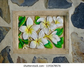 Flower sculpture on the wall. Flowers carved on brick walls. Frangipani flowers, Popular flowers in Thailand and Bahli, used in home decor, spa salon. Plumeria flower shape on the wall.