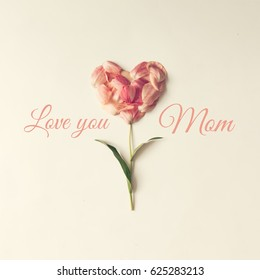 """Flower in shape of a heart made of tulip petals with text """"Love you Mom"""" Mothers day concept."""
