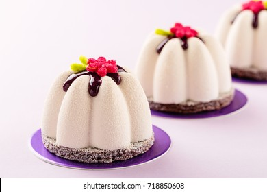 Flower shape mini mousse pastry dessert covered with white chocolate velour and decorated with glaze on pink background. Modern european cake. French cuisine