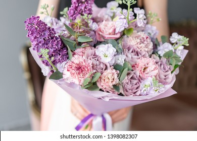 Flower shop. Beautiful bouquet of mixed flowers in woman hand. the work of the florist at a flower shop. Delicate Pastel color. Fresh cut flower. Pink and lilac color