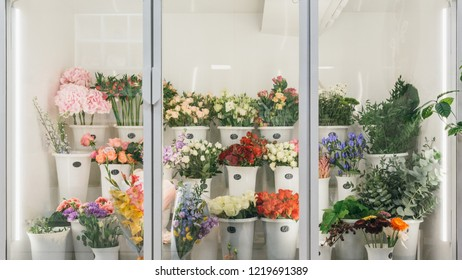 Flower shop concept. Different varieties fresh spring flowers in refrigerator room for flowers. Bouquets on shelf, florist business.