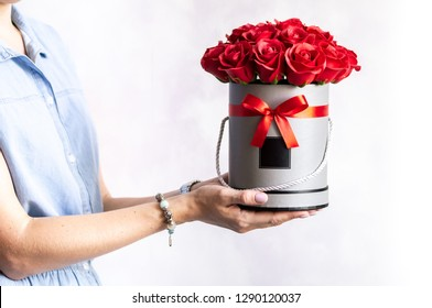 Flower shop: Florist girl showing off a bunch of red roses in a round gray box on a white background.