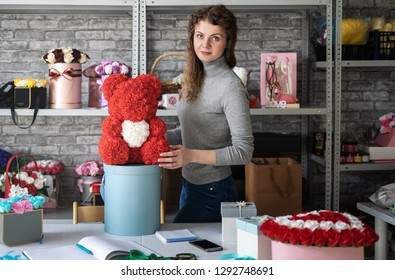 Flower shop: Florist girl shows a teddy bear of small red roses. Around the workshop and a lot of different floral bouquets.