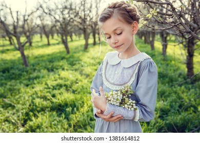 Flower spring series - nature after winter, apples or pears in bloom. Beautiful cute girls in the garden, enjoying the arrival of spring, dresses in vintage style. Concept of childhood, tenderness.