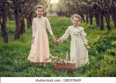 Flower spring series - nature after winter, apples or pears in bloom. Beautiful cute girls in the garden, enjoying the arrival of spring, dresses in vintage style. Concept of childhood, tenderne