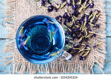 Flower tea of Butterfly pea (pea flowers, blue pea) for healthy drinking, detox drinking on old wooden table top view