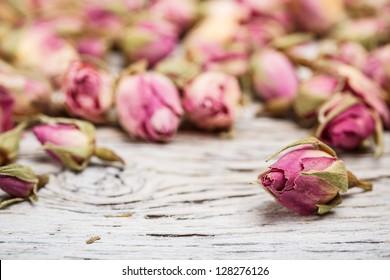 Flower tea rose buds on old wooden table