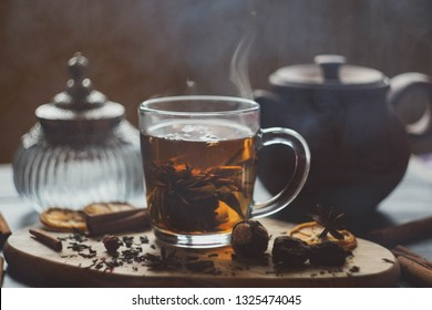 flower tea in a transparent mug with welding and spices/ vintage bottle and clay teapot