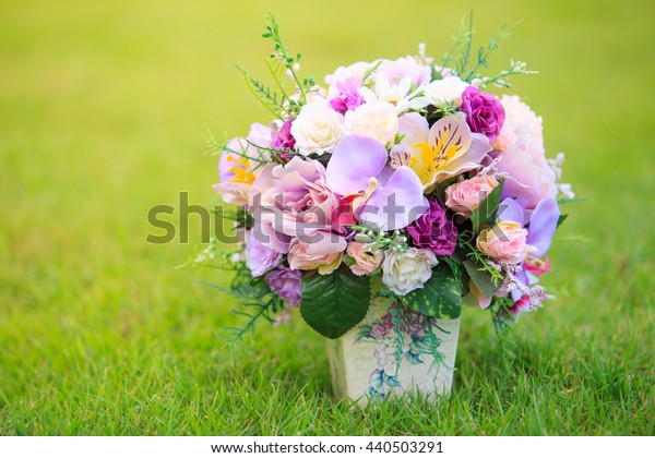 flower with vase isolated in field of green grass