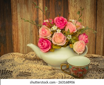 Flower in a white tea pot and vintage , cozy home rustic decor, cottage living tea pot and vintage cup of coffee on wooden background, cozy home rustic decor, cottage living