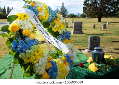 """Flower wreath with """"Beloved Husband, Father, and Grandfather"""" ribbon sash, with a burial urn and cemetery gravestones in the background, in an outdoor funeral scene"""