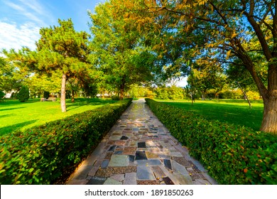Flowerbeds, Grass Pathway and Ornamental Vase in a Formal Garden.