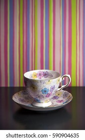 Flowered tea cup and saucer against striped wallpaper