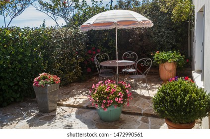 Flowered terrace with garden furniture in wrought iron and sunshade