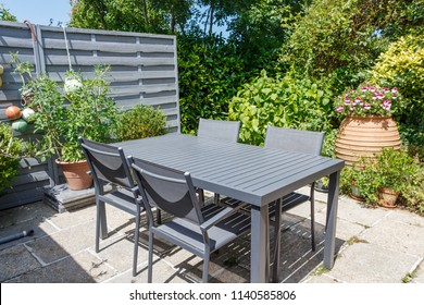 Flowered terrace with gray garden furniture during a sunny summer day