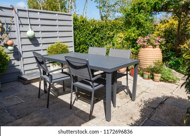 Flowered terrace with gray garden furniture during spring