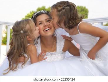 Flower-girls kiss the bride