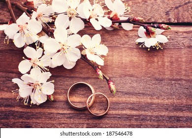 Flowering branch with white delicate flowers on wooden surface. Declaration of love, spring. Wedding card, Valentine's Day greeting. Wedding rings. Wedding bouquet, background. Empty wooden tabletop