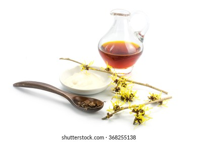 flowering witch hazel (Hamamelis), dried leaves, cream and essence for homemade skin care cosmetics and bath additive, isolated with shadow on a white background