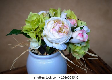 Flowerpot with artificial flowers on a table white and pink petals