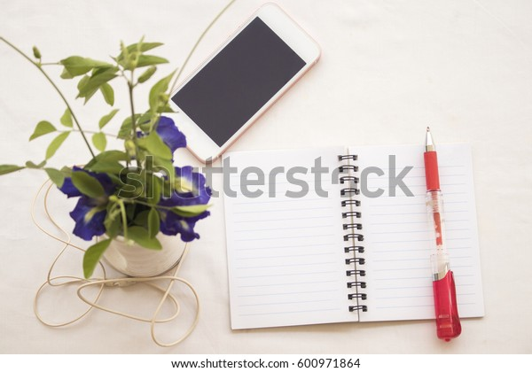 flowerpot with mobile and notebook on table white