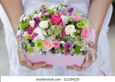 flowerpot with small pink, green and white flowers for wedding decoration at girl's hands