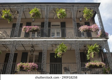 Flowerpots hanging from the balcony with exquisite ironwork at the French Quarter, New Orleans, Louisiana