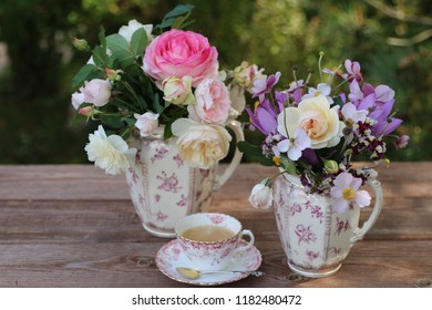 Flowers in antique faience pitcher, fresh coffee in vintage porcelain cup on aged table on fence background, garden scene, floral composition, morning light, vintage style